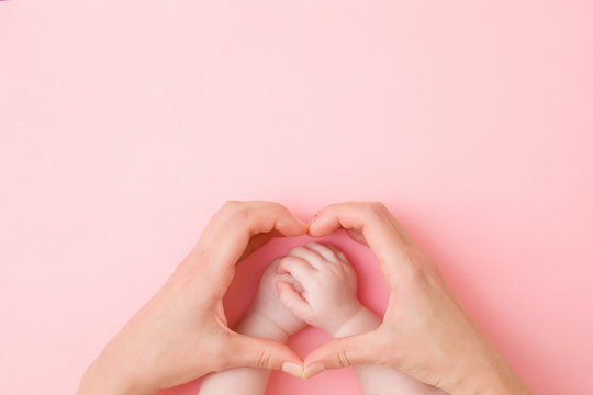 Heart shape created from young mother hands. Infant arms in middle. Light pink table background. Pastel color. Lovely emotional, sentimental moment. Empty place for text, quote or sayings. Top view.