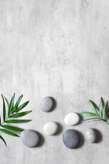Photo sur Toile Spa Grey spa background, spa concept, palm leaves and grey stones, top view.