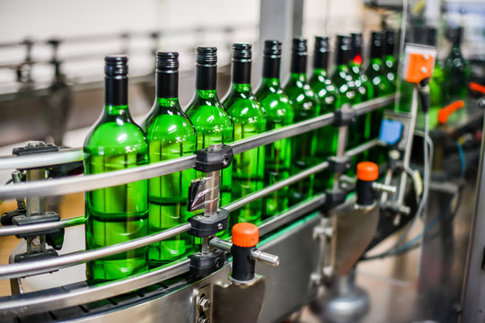 Bottling and conveyor line or belt at winery factory, Wine bottles filling production.