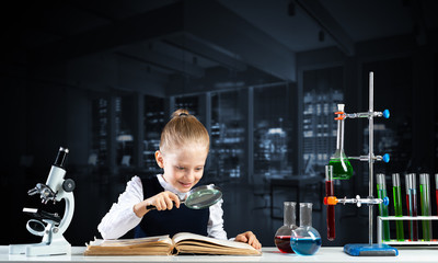 Little girl sitting at desk with magnifier