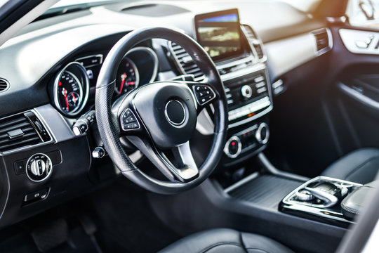 Interior view of car, Luxury car steering wheel and clean dashboard with display or monitor screen.