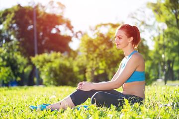 Beautiful smiling girl in sportswear relax in park