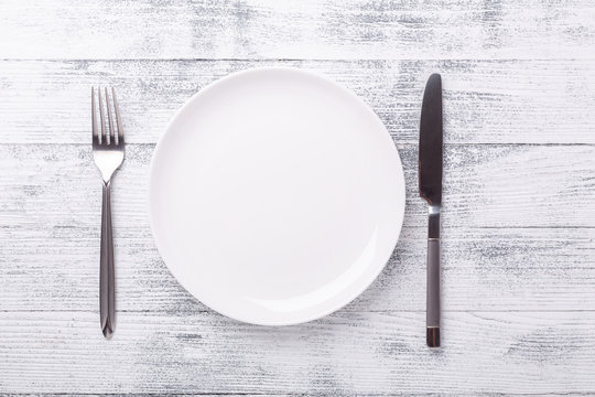 Empty white plate and cutlery on wooden background. Copy space. Top view