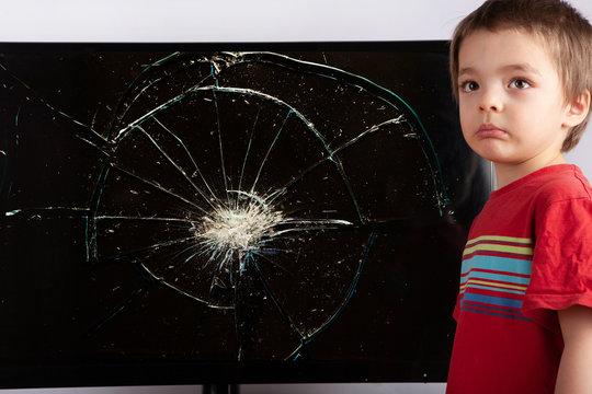 Sad little boy standing in front of a TV with broken screen after an accident. Home insurance concept.