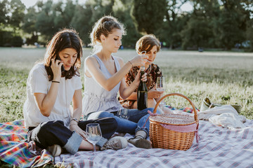 Mother and two daughters make picnic in a park at sunset in summer - A woman talking on the phone while the other opens the bottle of wine - Millennials having fun together