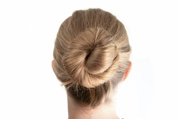 Simple bun hairstyle modeled by young white woman seen from behind close up shot isolated on white