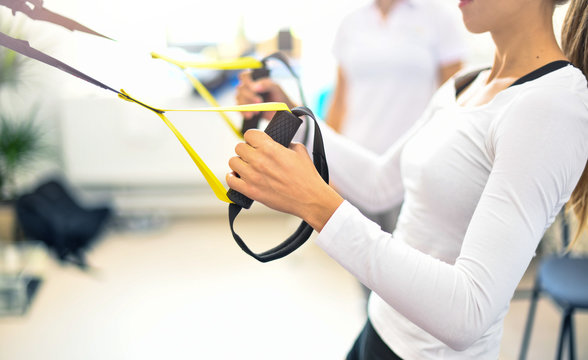 Trx fitness straps in the gym, Women training arms in activity centre.