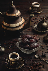 Turkish coffee with dates on a dark wooden table.