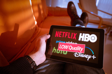 Barcelona, Spain. January 2019: Man holds a tablet with Netflix, hulu, amazon video, HBO and Disney plus logos on screen