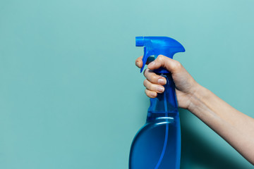 Close-up of female hand holding spray bottle for cleaning with blue pump, on cyan background.