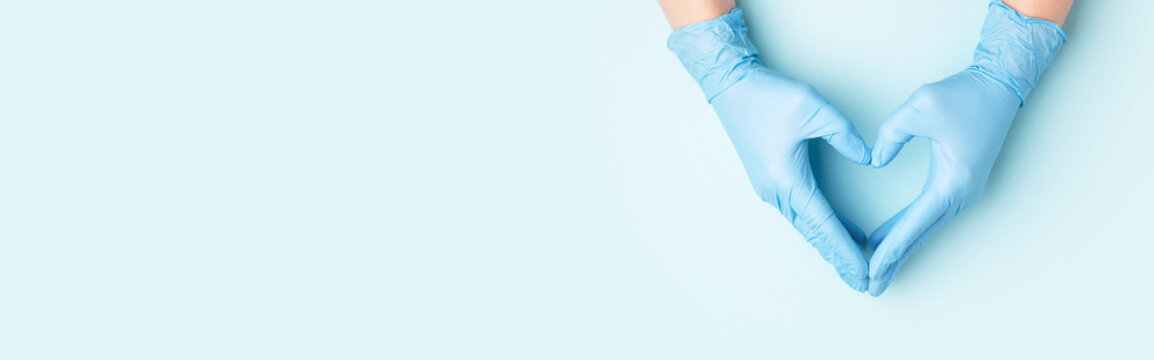 Hand in medical gloves in shape of heart on blue background.