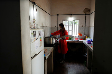 A volunteer wearing a face mask stirs the stew that she's preparing for the low-income people at a soup kitchen during the spread of the coronavirus disease (COVID-19), in Florencio Varela, in the outskirts of Buenos Aires