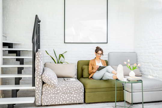 Young creative and well-dressed woman working on a digital tablet while sitting on the comfortable couch at home. Interior view on the modern and bright living room