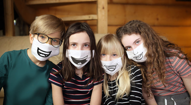 Children with face masks and painted drawings are quarantined at home