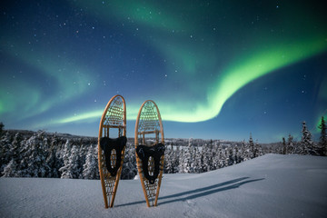 Snowshoeing under the northern lights, Yellowknife, Northwest Territories, Canada, North America