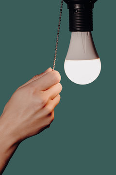 woman's hand turning off the light of a light bulb