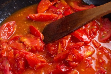 tomato frying on pan, cooking vegetable sauce, herbs.