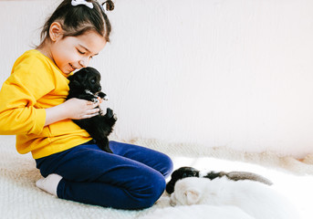 Indoor image of happy child playing at home with little dogs. Pretty little girl with the puppy. Adorable kid hugging, playing with her pet at the carpet in the room. Adoption of animal shelter