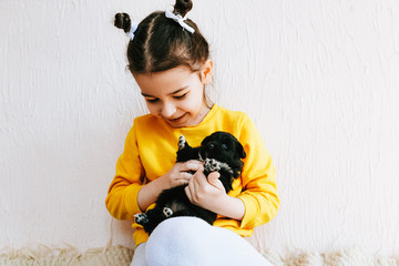 Indoor photo of a happy child smiling and playing at home with little dog. Cute little girl cares about the puppy. Adorable kid playing with her pet at the carpet in the room onm a sunny day.