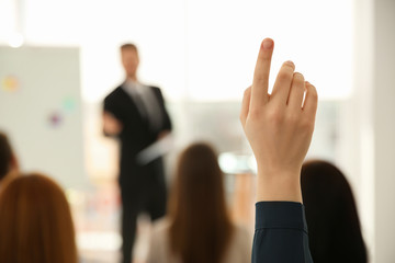 Young woman raising hand to ask question at business training indoors, closeup