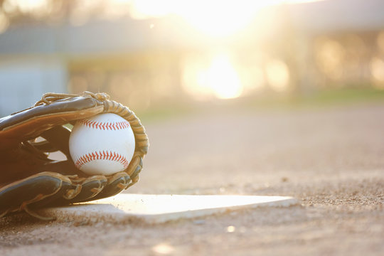 Baseball glove and ball on field during sunset with blurred background.