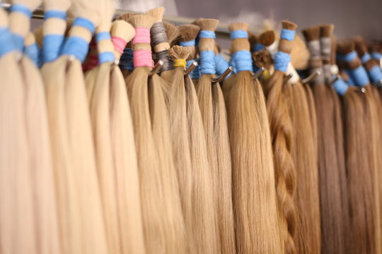 Various colors of straight single clip in human hair extensions. Making natural wigs.