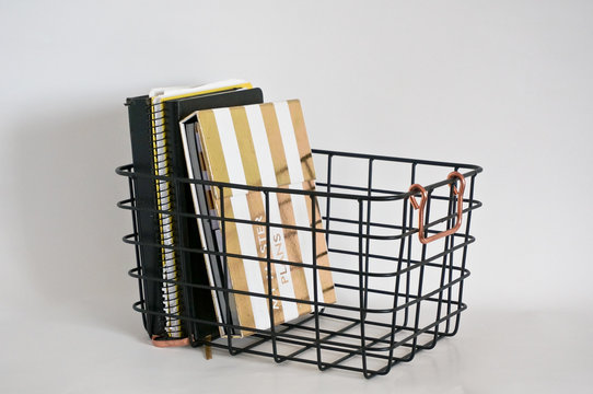 Black metal storage wire basket with bronze color handles white background, books and plnners