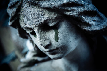Ancient stone statue of crying sad angel with tears in face as symbol of death and end of human...