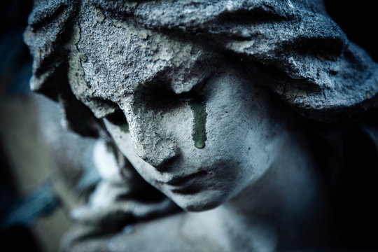 Ancient stone statue of crying sad angel with tears in face as symbol of death and end of human life.