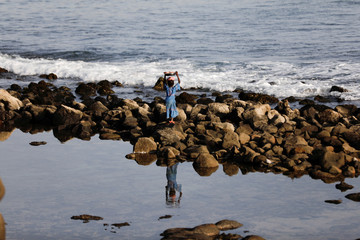 A girl carries a tray with peanuts to sell as she walks on the rocks amid the outbreak of the coronavirus disease (COVID-19), in Dakar