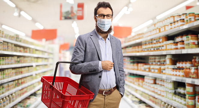 Bearded man shopping in a supermarket wearing a medical face mask