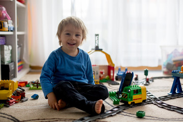 Adorable little boy playing with colorful plastic construction blocks at home, sitting on the...