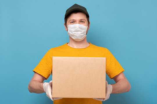 Young delivery man in nedical mask holding and carrying a cardbox on blue wall