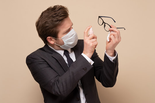 Man in medical mask wearing suit disinfecting the glasses.