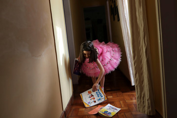 Alice, 5, grabs her books that fell down after her daily study session at home during a lockdown imposed by the state government because of the coronavirus disease (COVID-19) outbreak in Santo Andre