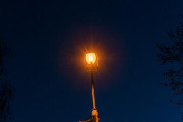 A street light at dusk. Sodium-vapor street lamp. Fotomurales