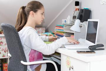 Dziewczynka pisze na laptopie zadanie