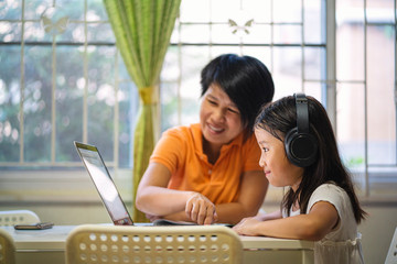 Asian girl and her teacher using laptop for online study during homeschooling at home. homeschooling, online study, home quarantine, online learning, corona virus or education technology concept