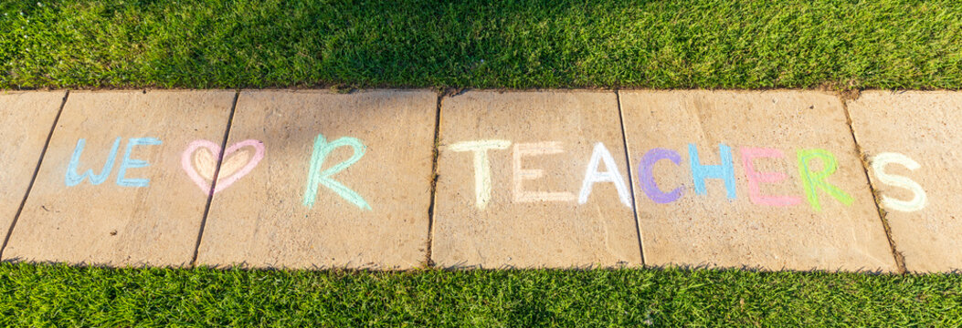 """The phrase """"We Love Our Teachers"""" written with sidewalk chalk, on gray concrete pavement background."""