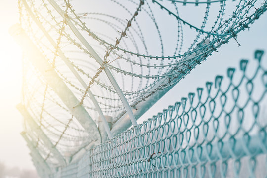 Border fence with barbed wire. Closing for quarantine. Maximum Security Detention Facility.