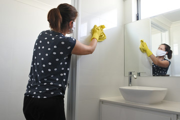 Adult woman with face mask and working rubber gloves cleaning and sanitizing home bathroom using disinfectant bleach cleaner to kill and prevent coronavirus spread Wall mural