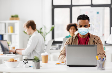 business and creative people concept - young indian man with laptop computer wearing protective medical mask for protection from virus disease working at office Fototapete