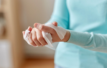 Papiers peints Pierre, Sable hygiene, health care and disinfection concept - close up of woman cleaning hands with antiseptic wet wipe
