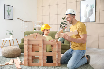 Father and little daughter dressed as builders playing with take-apart house at home