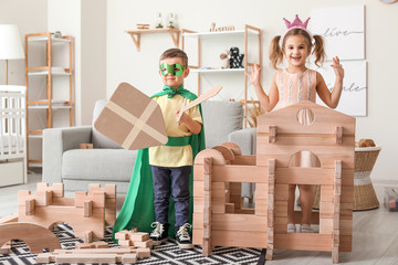 Little children in costumes playing with take-apart house at home
