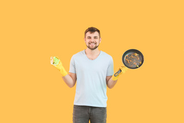 Man with dirty frying pan and sponge on color background