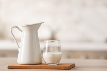 Glass and jug of fresh milk on table