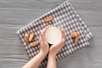 Woman with glass of fresh milk and cookies at table, top view