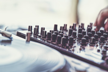 Part of a turntable and DJ mixer close-up with a blurred background
