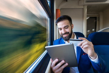Businessman sitting in comfortable passenger cabin and paying online with credit card while traveling by train. Internet banking and purchase. Online shopping on the go.